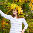 Happy young woman with autumn maple leaves garland in park. — Stock Photo