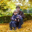 Happy father with little son having fun in autumn park. — Stock Photo