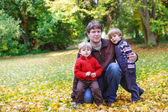 Happy father with two little sons having fun in autumn park. — Stock Photo
