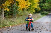 秋の森の自転車に乗って二歳のかわいい幼児男の子 — ストック写真