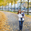 Adorable little son and mother in autumn city. — Stock Photo