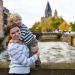 Adorable little son and mother in autumn city. — Stock Photo #34778715