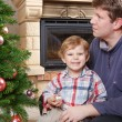 Father and little son decorating christmas tree at home — Stock Photo #34778805
