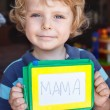 Little toddler boy with painting board writes his first word  — Zdjęcie stockowe