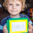 Little toddler boy with painting board writes his first word  — Photo
