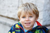 Portrait of little blond toddler boy smiling outdoors — Stock Photo