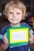 Muchacho del niño pequeño con la pintura bordo escribe su primera palabra — Foto de Stock