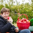 Young man eating red apples in an orchard — Photo