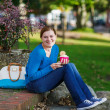 Young woman eating ice cream in summer park. — Stock Photo