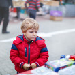 Stock Photo: Beautiful toddler boy in red clothes on flemarket.