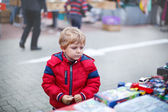 Beautiful toddler boy in red clothes on flea market. — Stock Photo