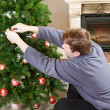 Young man decorating christmas tree at home with chimney. — Stock Photo