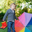 Little cute toddler boy with colorful umbrella and boots, outdoo — Stock Photo