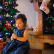 Little girl with lollipop and Christmas tree and decoration — Foto Stock