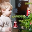 Little blond boy decorating Christmas tree at home. — Stock Photo