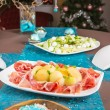 Holiday-decorated table, Christmas tree, ham and melone, and sal — Stock Photo #35885125