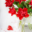 Red roses with heart decoration — Stock Photo