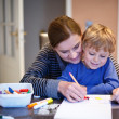 Stock Photo: Little blond boy and his mother making together preschool homewo