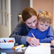 Little blond boy and his mother making together preschool homewo — Stock Photo #35885601