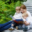 Woman and two little siblings sitting on bench in park and readi — Stock Photo
