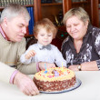 Little boy celebrating his birthday at home with his grandparent — Stock Photo