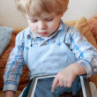 Stock Photo: Little toddler boy of two years playing with tablet pc .