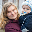 Young happy mother and her little baby boy on cold autumn day — Stock Photo