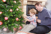 Father and little son decorating christmas tree at home — Stock Photo