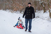 Two little siblings and their father having fun on sledge — Stockfoto