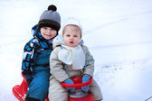 Two little siblings having fun on sledge — Zdjęcie stockowe