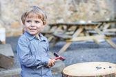 Malý Plavovlasý chlapec hraje s kladivem venku. — Stock fotografie