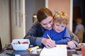 Little blond boy and his mother making together preschool homewo — Stok fotoğraf