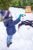 Adorable toddler boy having fun with snowman on winter day — Stockfoto