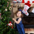 Stock Photo: Little girl being happy about christmas tree and lights