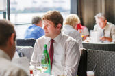 Young man sitting in restaurant on event party — Stock Photo