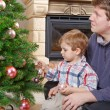 Father and little son decorating christmas tree at home — Stock Photo #37230273
