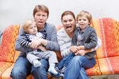 Familie van vier zittend op een bankje in home garde — Stockfoto
