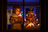 Little boy standing by winter at Christmas time and holding cand — Stock Photo
