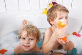 Two little twins boys having fun with water by taking bath in ba — Foto de Stock