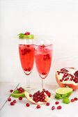 Two glasses with red pomgranate champagne, lime and mint. — Stockfoto
