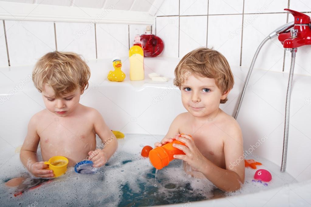 两个小的双胞胎男孩玩水由广管局在考虑浴
