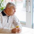Portrait of senior man near window, indoor — Stock Photo