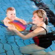 Stock Photo: Little baby with blue eyes learning to swim