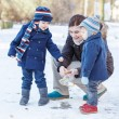 Mother and two little siblings boys feeding ducks in winter. — Stock Photo #39679727