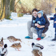 Mother and two little siblings boys feeding ducks in winter. — Stock Photo