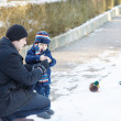 Stock Photo: Father and little son feeding ducks in winter.