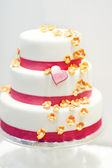 Wedding cake decorated with pink rose flowers and hearts . — Stock Photo