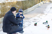 Father and little son feeding ducks in winter. — Stock fotografie
