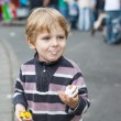 Stock Photo: Little boy of three years eating at funfair, outdoors