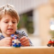 Little blond boy playing with cars and toys at home, indoor. — Stock Photo